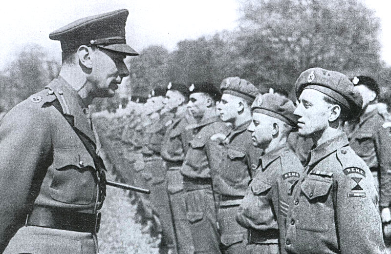 This is a photograph of HM King George VI speaking with a REME soldier at the parade of the 44th Regiment Royal Armoured Corp 22nd April 1944